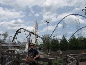 Man in front of a giant roller coaster
