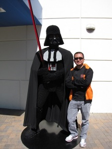 Man standing beside Darth Vader
