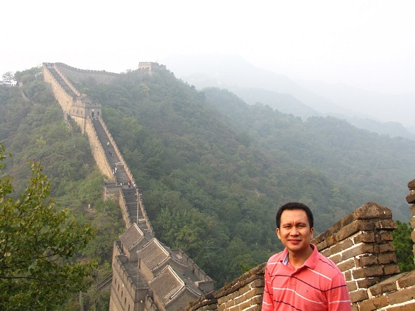 A man in red standing on the Great Wall of China