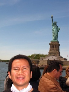 A man's face with the Statue of Liberty at the background